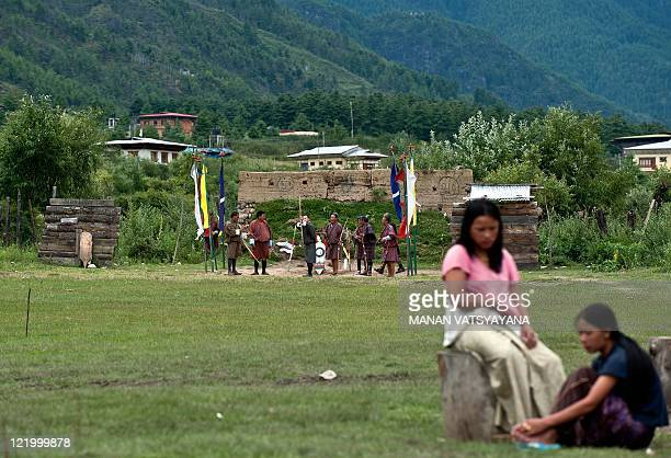 Bhutanese women sit on a field as local villagers take part in a game of archery in Paro on August 21 2011 Archery an ancient traditional sport is...