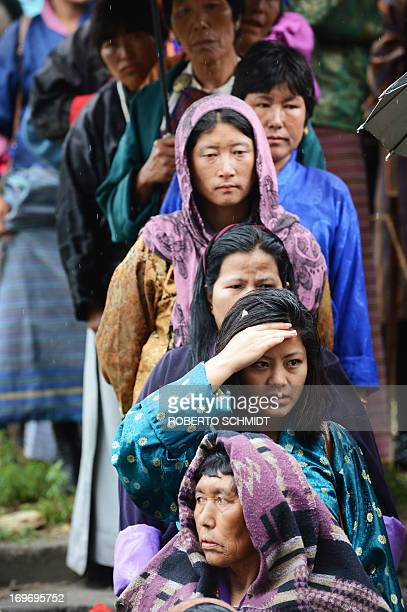 Bhutanese women stand in line outside a polling station as they line up to vote in Paro on May 31 2013 Bhutan begins its second ever parliamentary...
