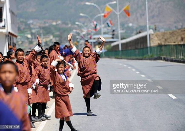 Bhutanese youth dance and gesture as they line up to welcome the Indian Prime Minister Manmohan Singh arriving to attend the 16th SAARC summit in...