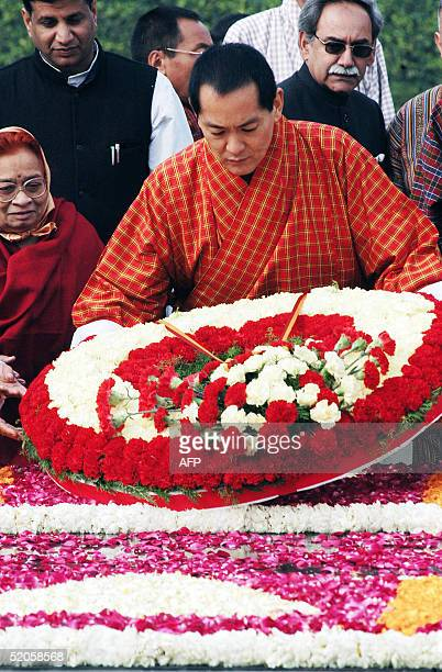 Bhutan's King Jigme Singye Wangchuck places a flower wreath to pay homage to India's father of the nation Mahatma Gandhi's memorial in New Delhi 25...