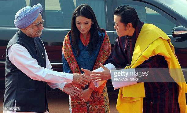 Bhutan's Queen Jetsun Pema watches as King Jigme Khesar Namgyel Wangchuck shakes hands with Indian Prime Minister Manmohan Singh during a ceremonial...