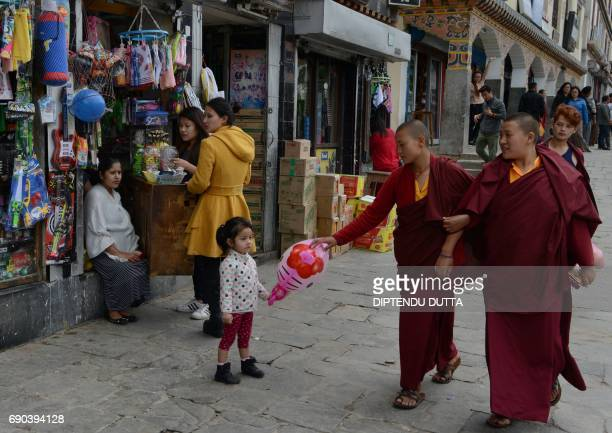 Bhutanse monks walk past shopkeepers in Thimpu on May 31 2017 Japanese Princess Mako is scheduled to arrive on a nineday official visit to Bhutan...