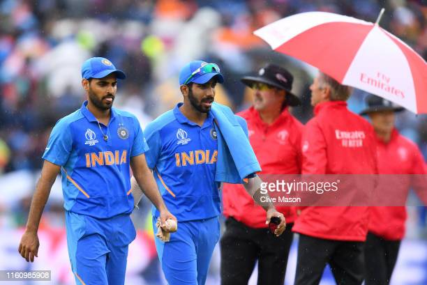 Bhuvneshwar Kumar and Jasprit Bumrah India leave the pitch as rain delays play during the Semi-Final match of the ICC Cricket World Cup 2019 between...