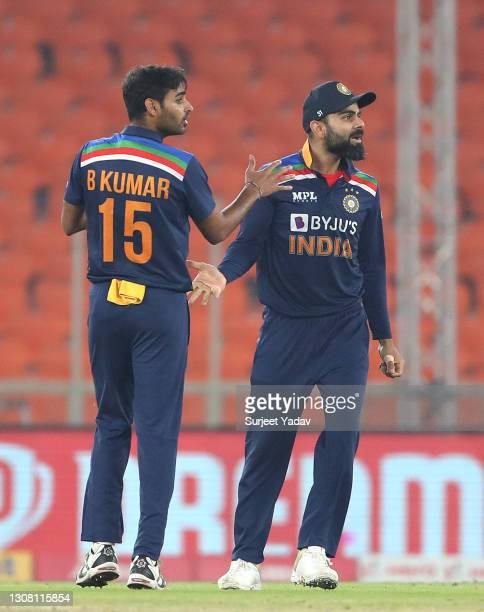 Bhuvneshwar Kumar celebrates the wicket of Jos Butler of England with captain Virat Kohli during the 5th T20 International between India and England...