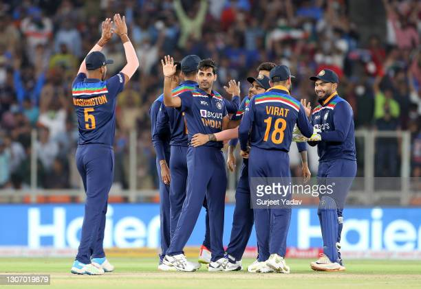 Bhuvneshwar Kumar of India celebrates after taking the wicket of Jos Buttler of England with team mate Washington Sundar during the 2nd T20...