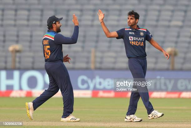 Bhuvneshwar Kumar of India celebrates after taking the wicket of Jason Roy of England with team mate Rohit Sharma during the 3rd One Day...