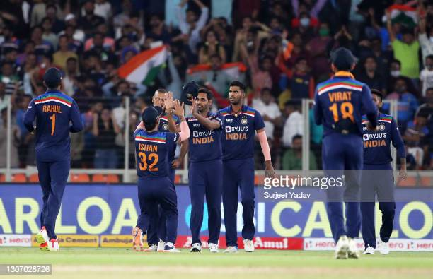 Bhuvneshwar Kumar of India celebrates with team mate Ishan Kishan after taking a catch to dismiss Jason Roy of England during the 2nd T20...
