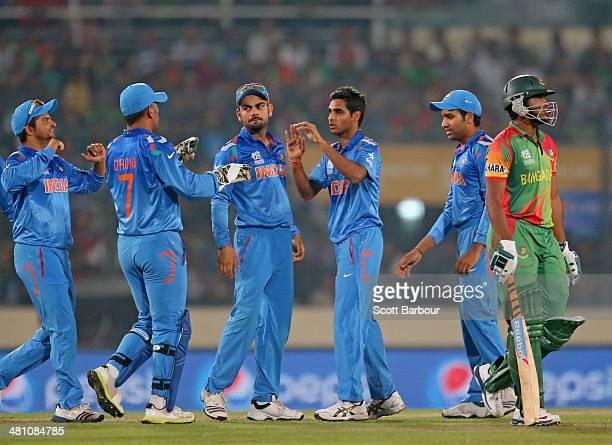 Bhuvneshwar Kumar of India is congratulated by his teammates after dismissing Shakib Al Hasan of Bangladesh during the ICC World Twenty20 Bangladesh...
