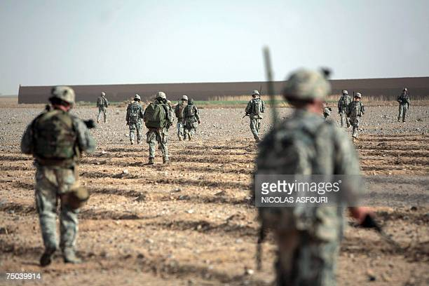 Biabanak, AFGHANISTAN: US soldiers from Bravo Company 1-508 Parachute Infantry Regiment 82nd Airborne Division walk across a field as they search...