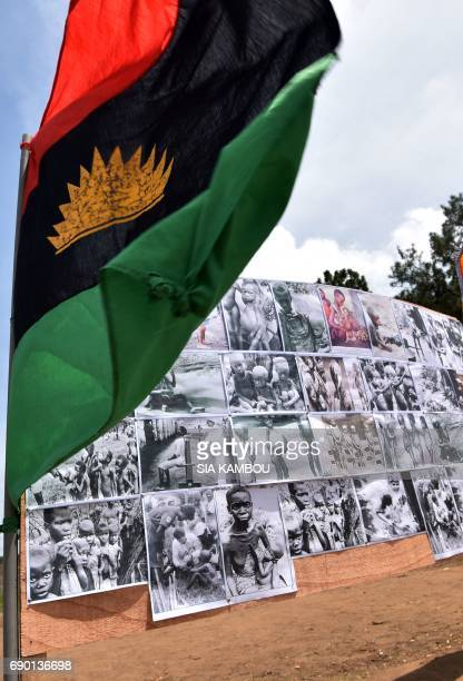 A Biafra flag flies beside a placard on May 30 2017 in Abidjan during commemorations of the 50th anniversary of the Nigerian civil war Nigeria on May...