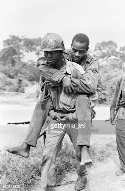 A Biafran soldier seen here carrying an injured comrade during the Biafra conflict 11th June 1968