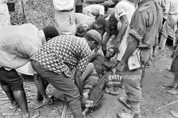 Biafran soldiers and helpers seen here carrying an injured comrade onto a stretcher during the Biafra conflict 11th June 1968
