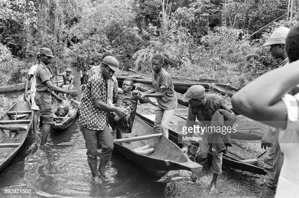 Biafran soldiers and helpers seen here carrying an injured comrade onto a canoe to cross the river during the Biafra conflict 11th June 1968