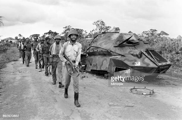 Biafran soldiers seen here marching past a destroyed Nigerian army armoured personnel carrier during the conflict 11th June 1968