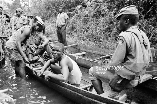 Biafran soldiers seen here transferring a captured Nigerian soldier across the river in a canoe during the Biafran conflict 11th June 1968