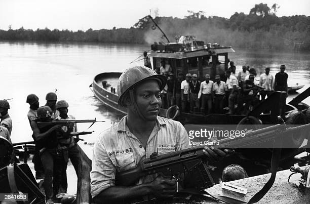 Biafran soldiers with rifles aboard army tugs during the Nigerian Biafran War