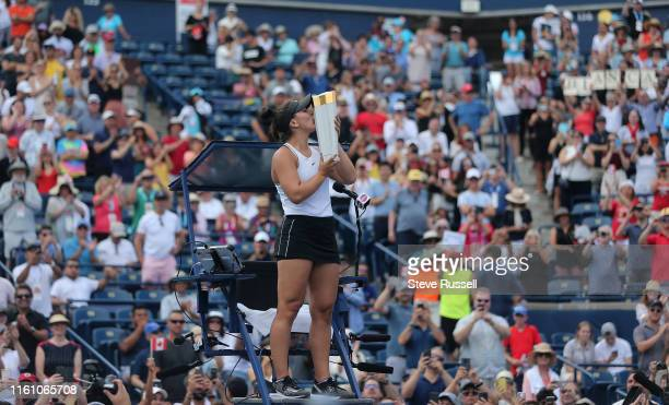 TORONTO ON AUGUST 11 Bianca Andreescu raises the trophy to the crowd from atop the judges chair Bianca Andreescu from Canada wins the Rogers Cup...