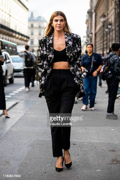 Bianca Brandolini d'Adda, wearing a black crop top, black pants and black floral print blazer, is seen outside the Giambattista Valli show during...