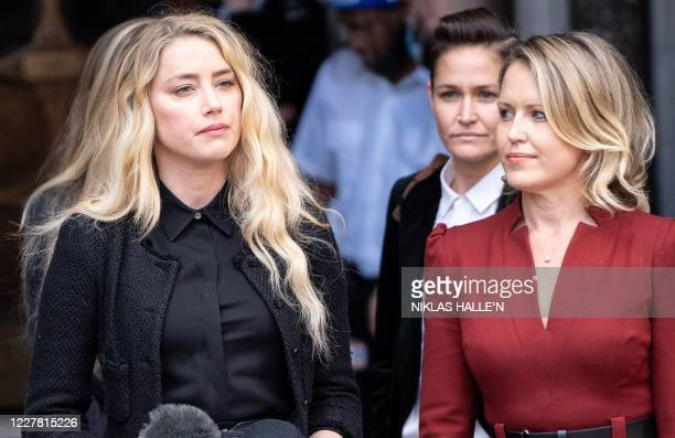 Bianca Butti , partner of US actress Amber Heard , listens as Heard makes a statement to members of the media outside the High Court, following the...