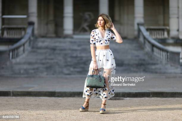 Bianca Derhy fashion blogger from Bibi Goes Chic wears an Asilio flower print dress a Coach green bag and Michael Kors shoes during Paris Fashion...