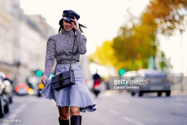 Bianca Derhy wears a black hat gray turtleneck top a ruffle skirt black high boots a bag outside Valentin Yudashkin during Paris Fashion Week...