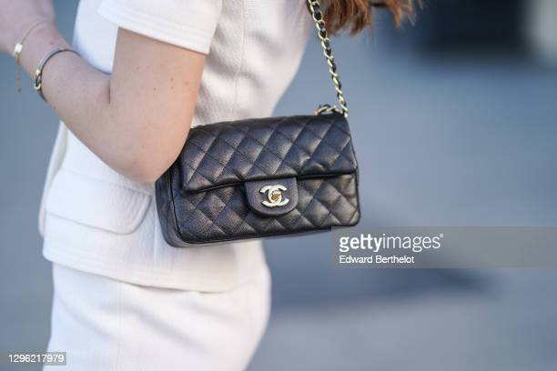 Bianca Derhy wears a black leather quilted Chanel bag, a white Chanel skirt, on January 10, 2021 in Paris, France.