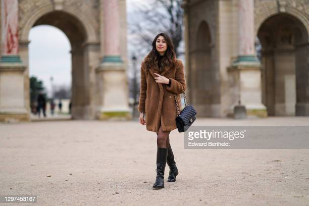Bianca Derhy wears a brown fluffy faux fur long winter coat from Max Mara, a black leather quilted Chanel bag, a black turtleneck pullover, tights,...