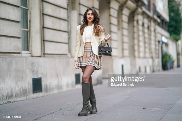 Bianca Derhy wears a cream-color wool blazer jacket / cardigan from Vertigo, a white wool cropped pullover / sweater from Majorelle, a black leather...
