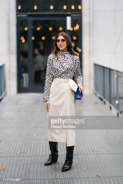 Bianca Derhy wears sunglasses, earrings, a hi-neck white and black spotted draped long sleeves top, a blue quilted bag, a cream-color leather...