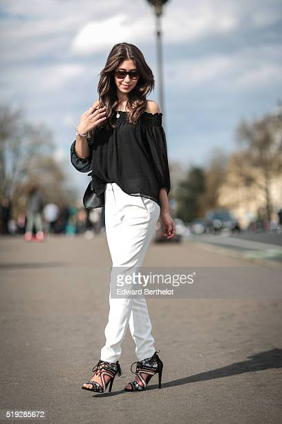 Bianca Dhery is wearing The Kooples white pants Kurt Geiger shoes a Dior bag a Zara black top and sunglasses during a street style session in the 7th...