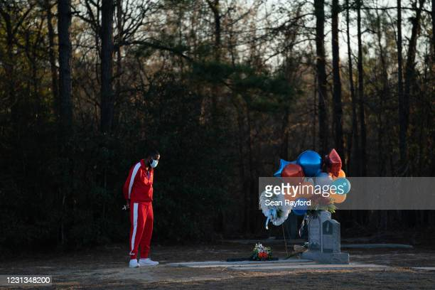 Bianca Dorsey visits the gravesite of Ahmaud Arbery during a candlelight vigil at New Springfield Baptist Church on February 23, 2021 in Waynesboro,...
