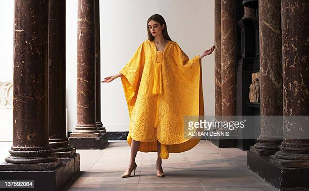 Bianca Gavrilas models a handembroidered cape made from the naturally golden silk of the Orb spider during a photocall at The Victoria Albert Museum...