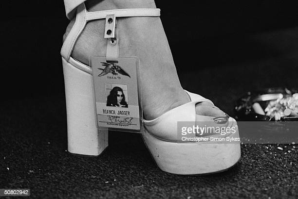 Bianca Jagger displays her backstage pass, which is attached to her white platform shoe, during the Rolling Stones' 1975 Tour of the Americas.