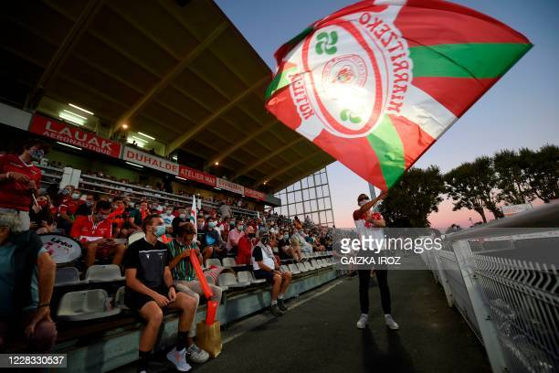 Biarritz rugby fan, wearing a protective mask, waves a flag as he attends the first French Pro D2 Championship official rugby match between Biarritz...