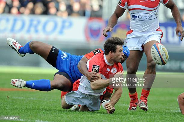 Biarritz's French fly-half Julien Peyrelongue is tacled during the French Top 14 rugby union match Grenoble vs Biarritz on November 1, 2012 at the...
