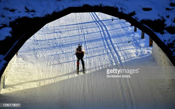Biathlete speeds through a tunnel as he competes during the men's 10 km IBU Biathlon World Cup in Hochfilzen, Austria, on December 17, 2020. /...