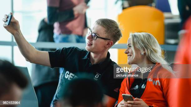 Biathletes Johannes Kuehn and Maren Hammerschmidt take a selfie at the checkin desk in Munich Germany 5 February 2018 The German Olympic team is...