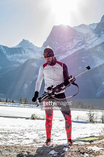 Biathlon athlete prepares to aim competition rifle