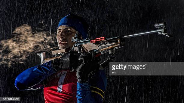 Biathlon competitor preparing for target shooting at night