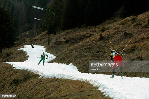 Biathlon Competitors ski across a barren landscape on trails of artificial snow due to a complete lack of natural snow during a Biathlon World Cup