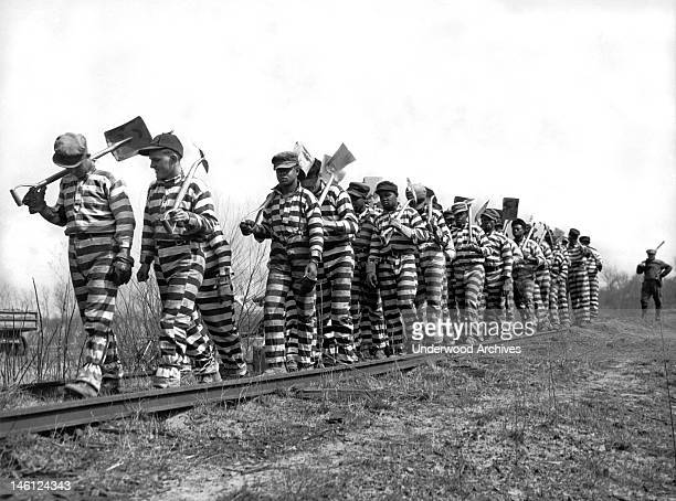 Bibb County chain gang with picks and shovels returns from work for the day, Macon, Georgia March 8, 1937. The county recently instituted an eight...