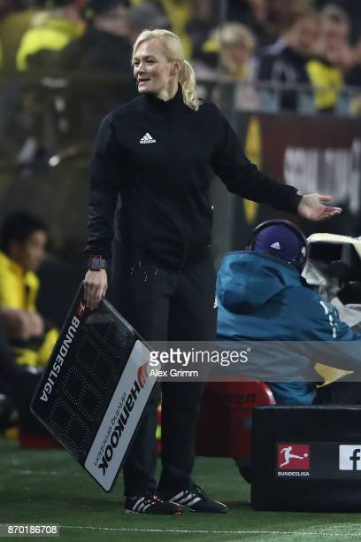 Bibiana Steinhaus holds the sign for substitutions and smiles during the Bundesliga match between Borussia Dortmund and FC Bayern Muenchen at Signal...