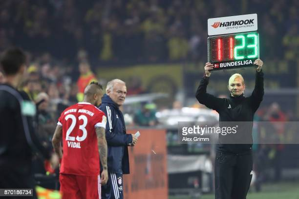 Bibiana Steinhaus holds the sign for substitutions as Arturo Vidal of Bayern Muenchen is about to come on during the Bundesliga match between...