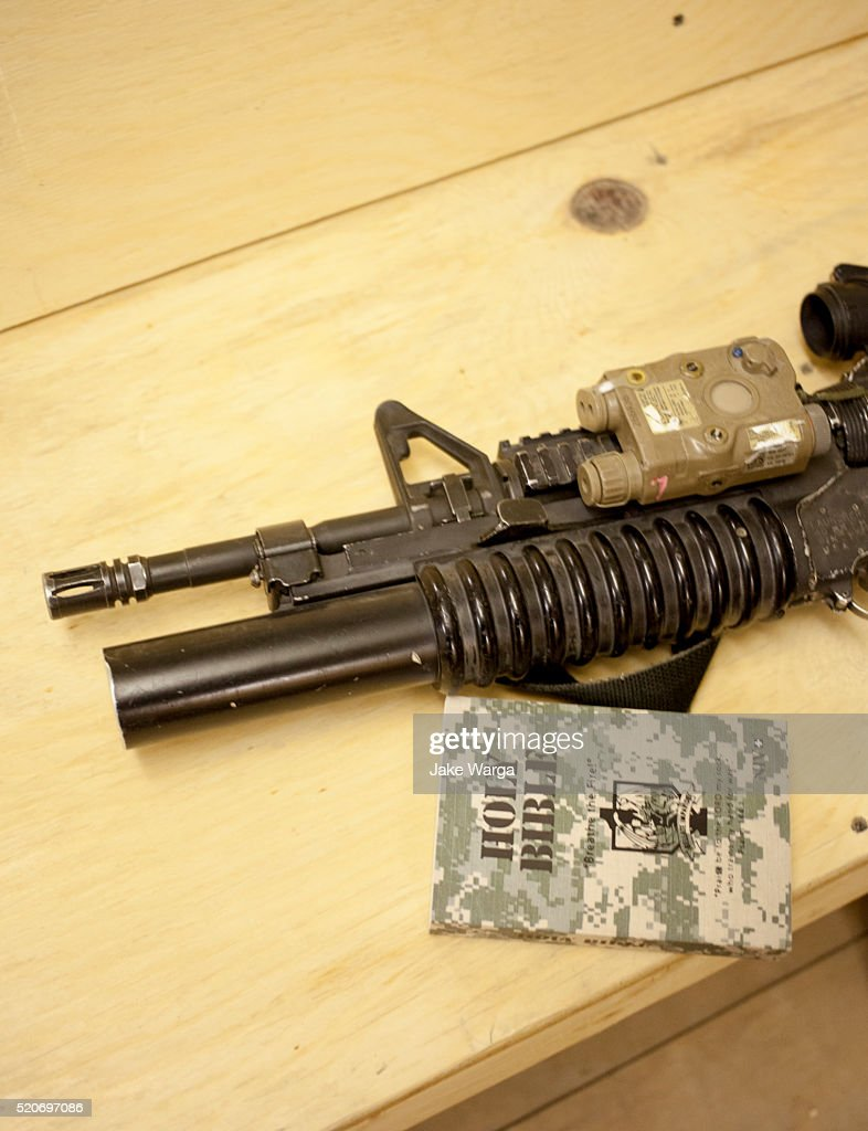 Bible and Weapon on chapel pew, U.S. Army Base, Afghanistan : Stock Photo