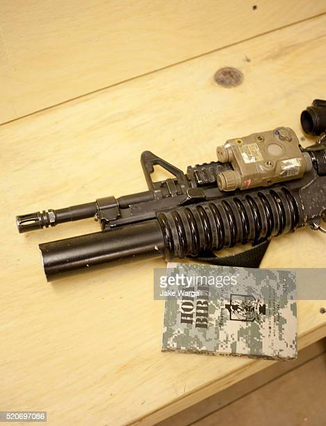 bible and weapon on chapel pew, u.s. army base, afghanistan - jake warga stock photos and pictures