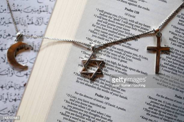 Bible, Coran and symbols of islam, judaism and christianity. France.