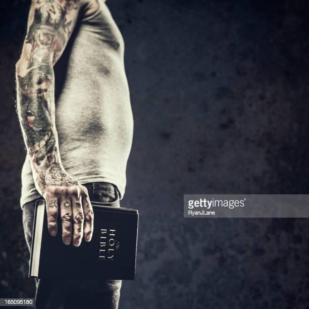 Bibel in den Armen von Tattooed Mann