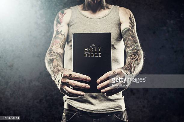 bible in arms of tattooed man - gospel stock photos and pictures