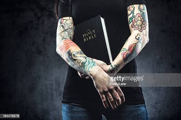 bible in arms of tattooed woman - christianity stock pictures, royalty-free photos & images
