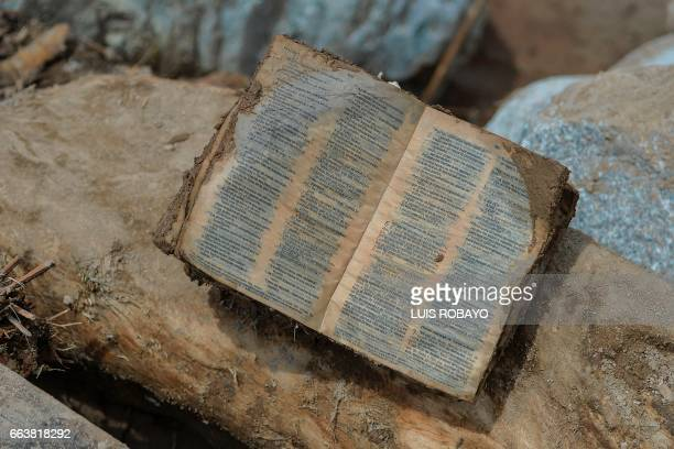 A Bible is seen among the rubble left by mudslides following heavy rains in Mocoa Putumayo department southern Colombia on April 2 2017 The death...